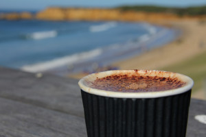 Take away coffee with cliffs and coast in the background